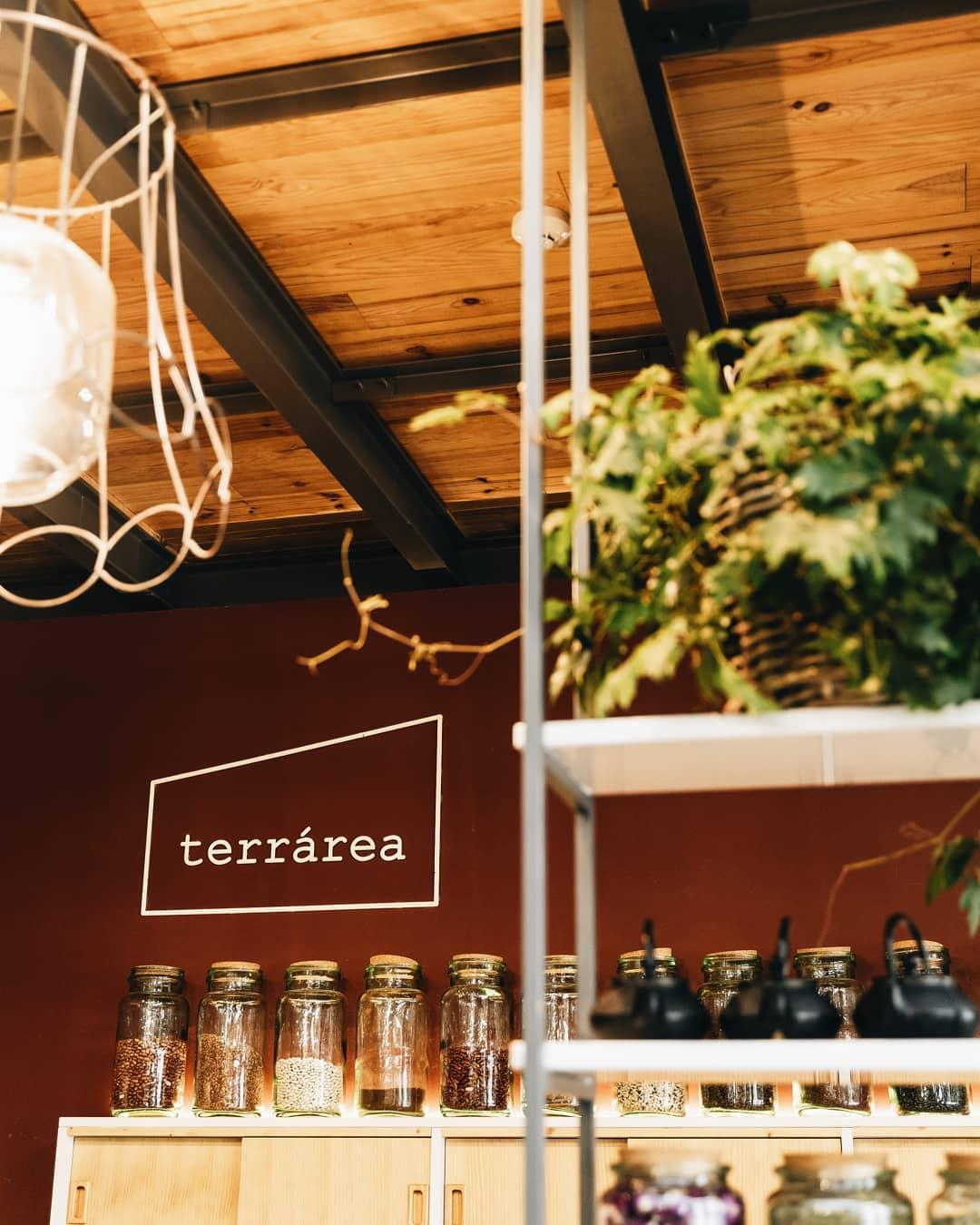Vista para trás do balcão do Restaurante vegetariano da Terrárea, com vários frascos de leguminosas e o logotipo da Terrárea em grande destaque.