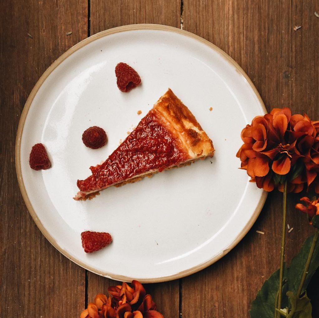 Fatia de Bolo Cheesecake de amora, com duas flores decorativas.