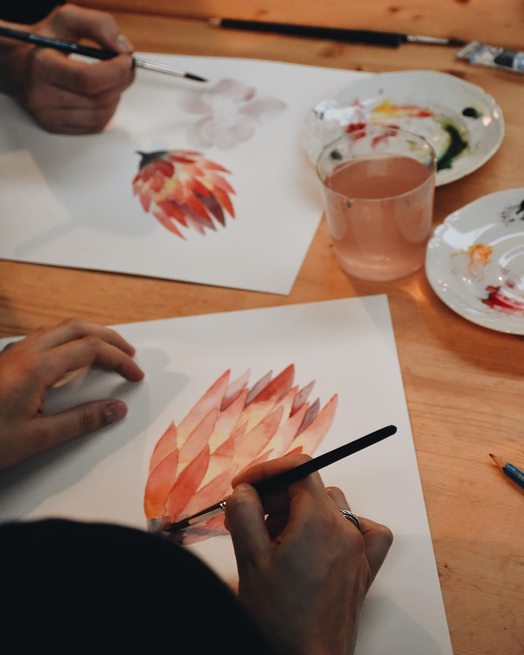 Senhora a pintar em aguarela uma flor, em workshop da Terrárea de pintura em aguarela de flores
